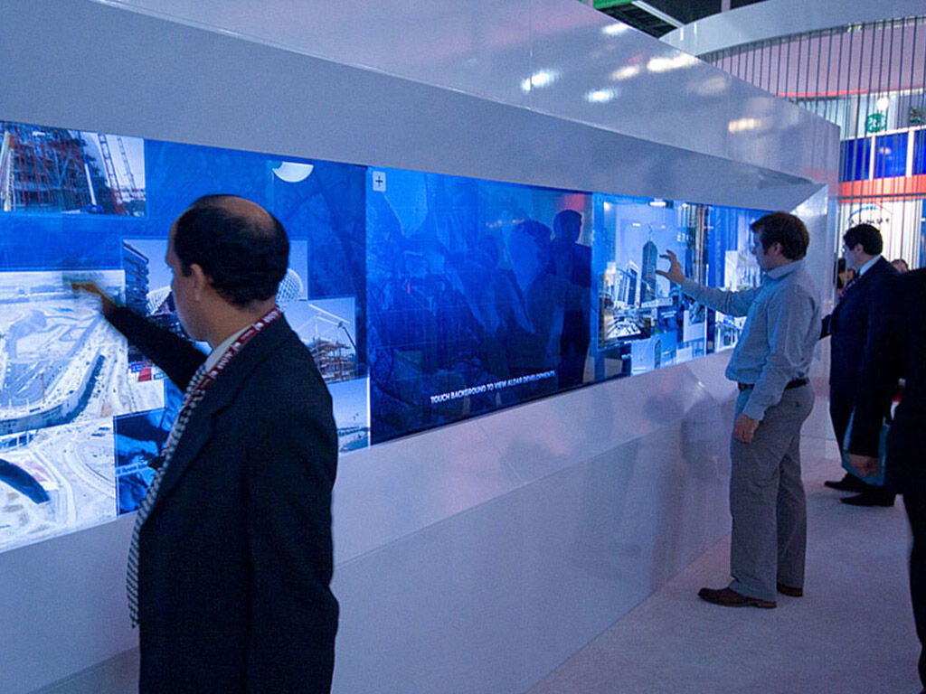 Three people using a 20ft multi touch screen