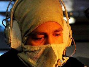A sailor using a headset with fire retardant clothing
